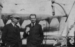 Two men in suits standing on deck