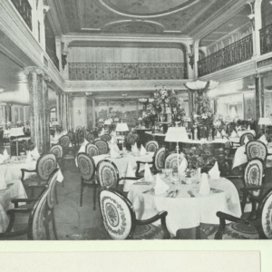 An ornate restaurant with tables featuring tablecloths, napkins, lamps and table settings