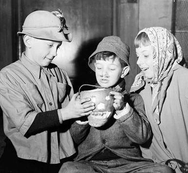 Three children in costume gathered around a lantern