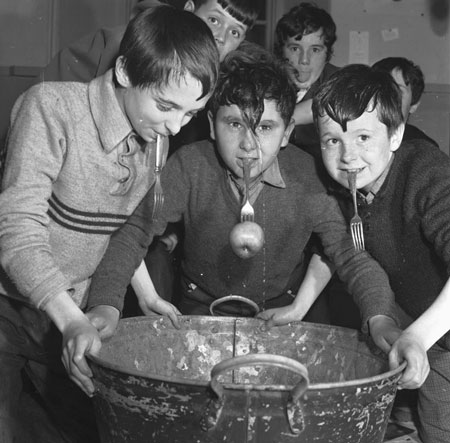 Three boys leaning over a bucket with forks in their mouths, one with an apple on the end